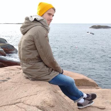 Tammo Schwier, sitzend auf einem Stein am Meer